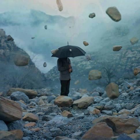 Persona con sombrilla resguardándose de piedras cayendo.
