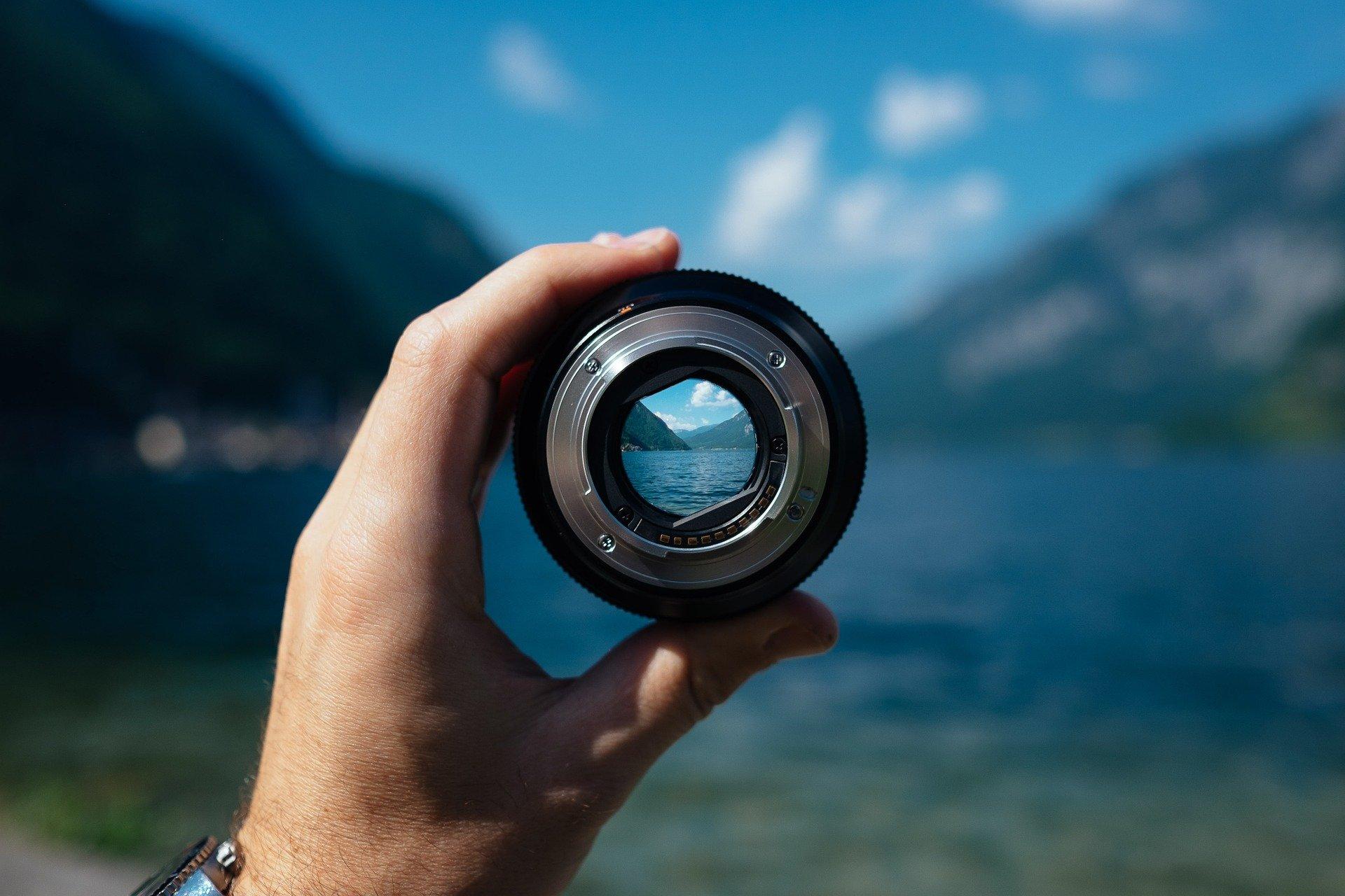 Mano agarrando lente fotográfico contra paisaje de un lago y montañas